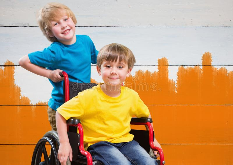 Disabled boy in wheelchair with friend with bright orange painted background stock photos
