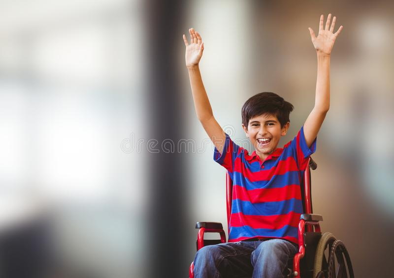 Disabled boy in wheelchair in front of blurred background royalty free stock photo
