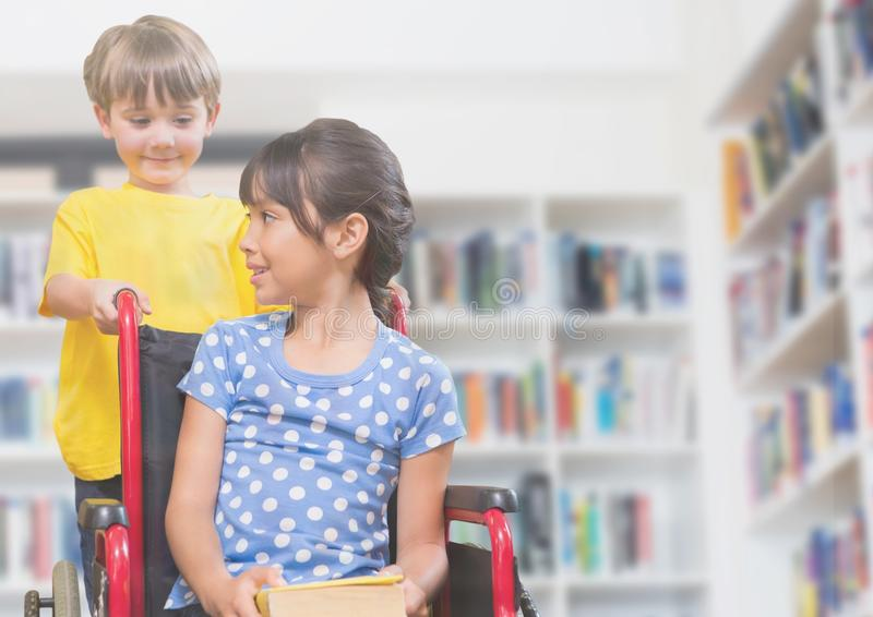 Disabled girl in wheelchair with friend in school library stock images