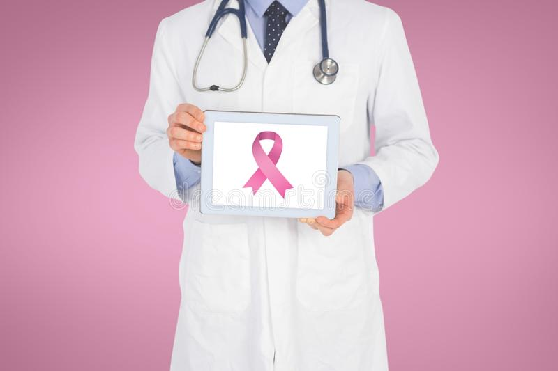 Doctor holding a tablet with a breast cancer awareness ribbon on screen. Digital composite of Doctor holding a tablet with a breast cancer awareness ribbon on royalty free stock photography