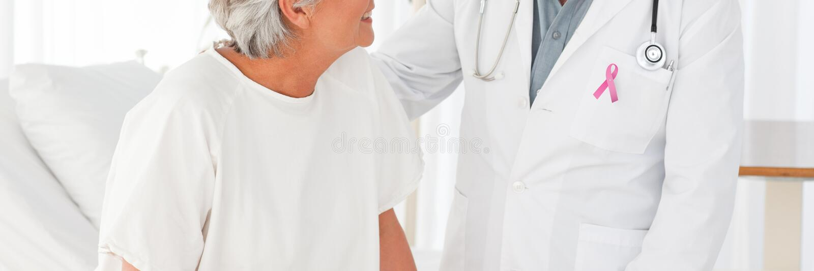 Doctor man with breast cancer awareness ribbon with patient stock photos