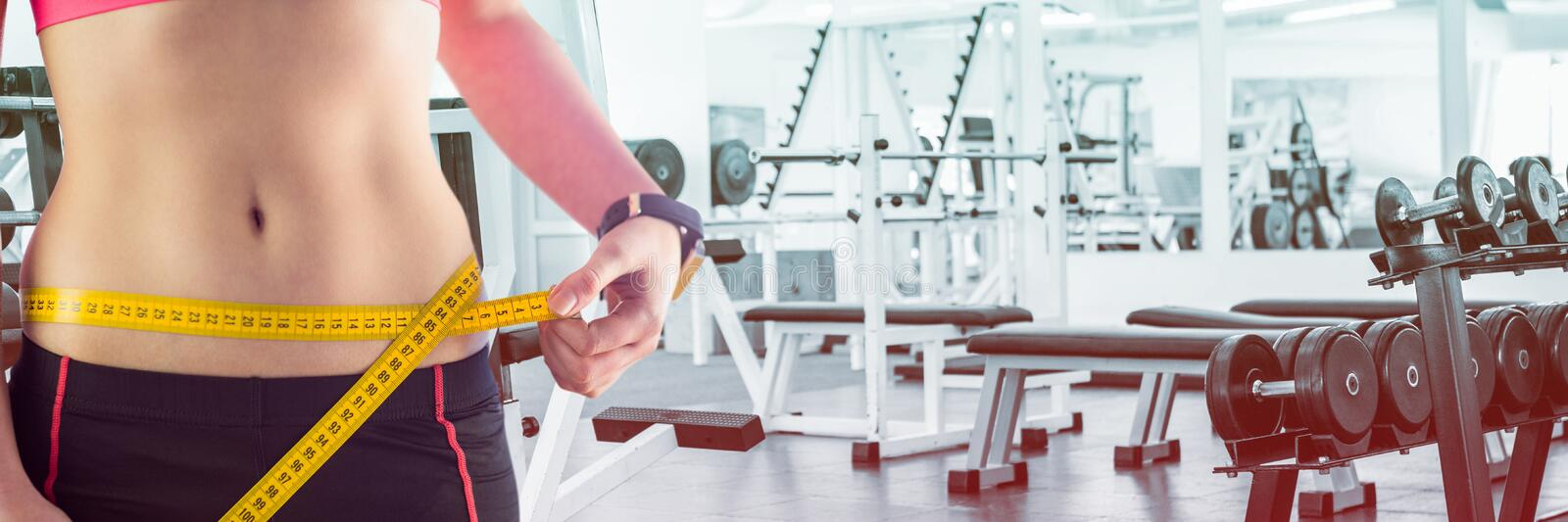 Fit Woman with measuring tape around waist in fitness studio royalty free stock photos