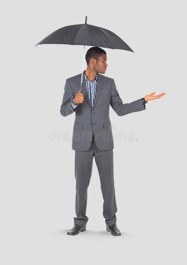 Full body portrait of man holding umbrella standing with grey background stock photos