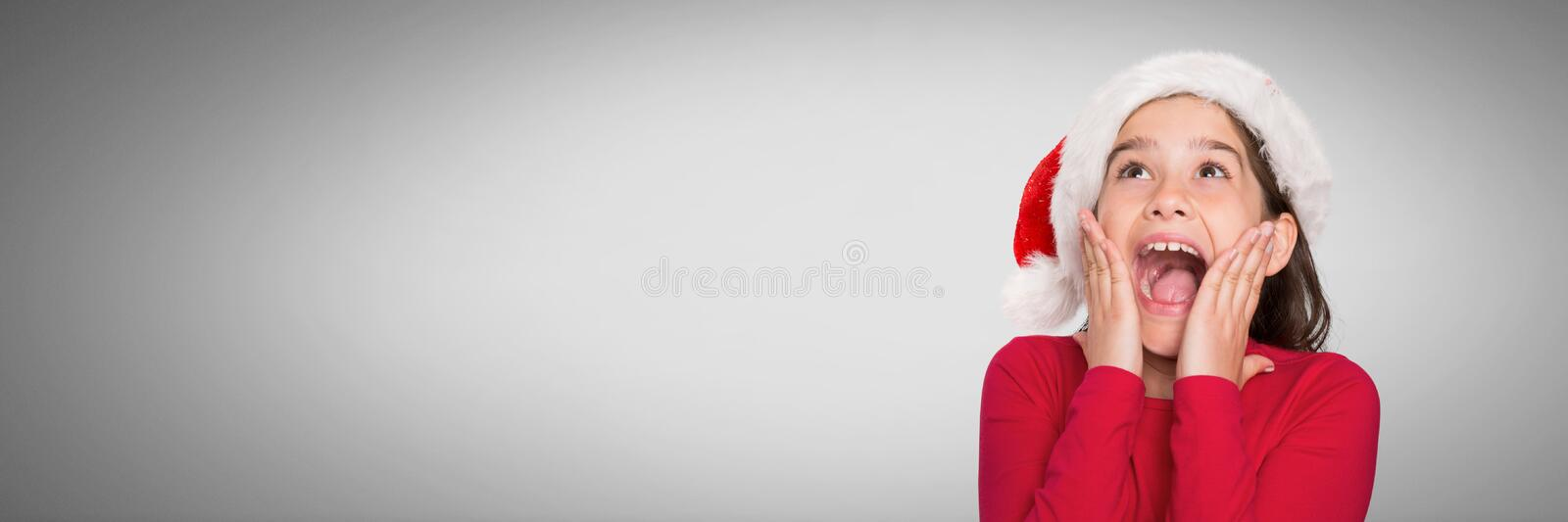 Girl against grey background with Santa hat amazed and surprised looking up stock illustration
