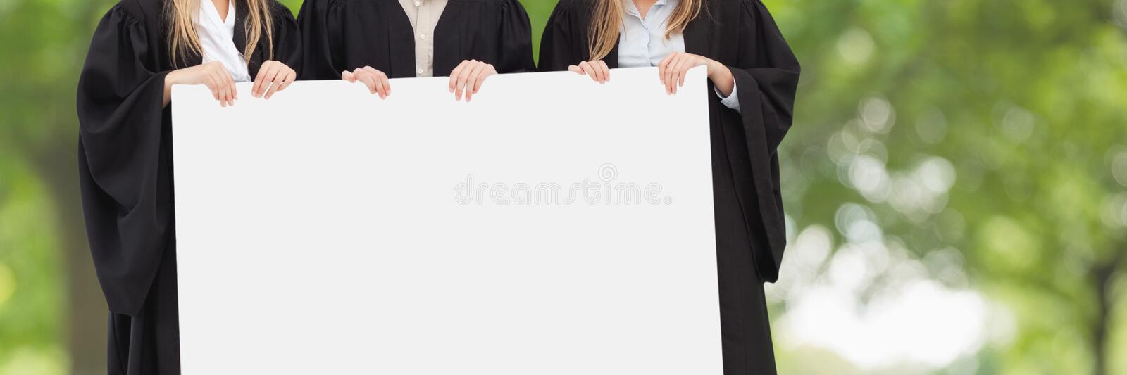 Graduated people holding a blank card against green blurred background royalty free stock photos