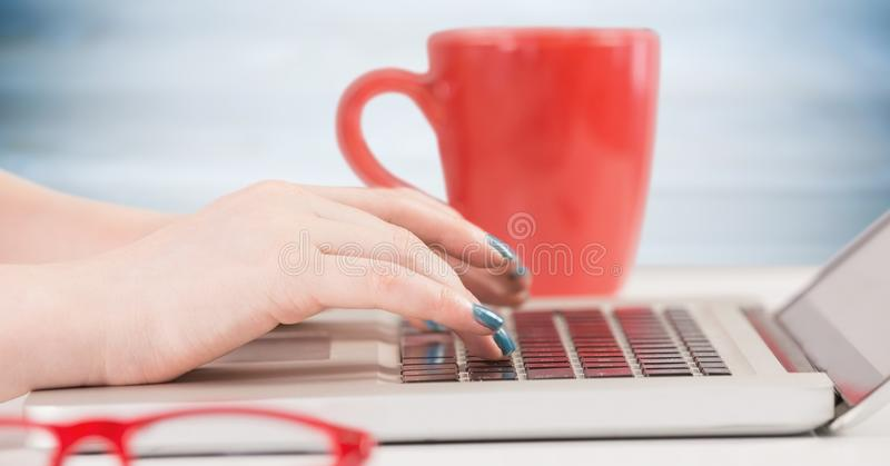 Hands with laptop and red coffee cup against blurry blue wood panel. Digital composite of Hands with laptop and red coffee cup against blurry blue wood panel stock images