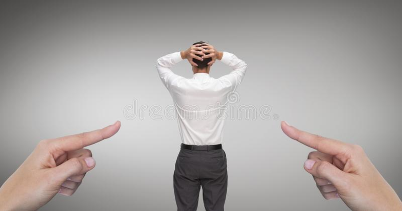 Hands pointing at surprised business man against grey background royalty free stock photography