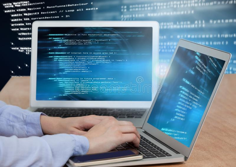 Hands typing coding text on two laptops stock image