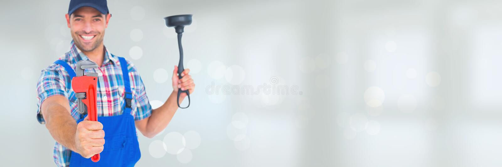 Happy plumber man holding a plunger and a wrench against white background with flares. Digital composite of Happy plumber man holding a plunger and a wrench royalty free stock image