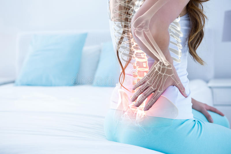 Digital composite of highlighted spine of woman with back pain stock image