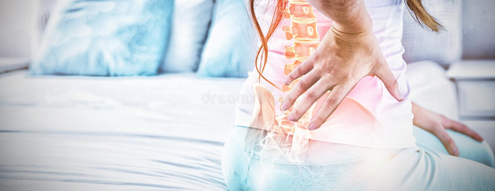 Digital composite of highlighted spine of woman with back pain. At home royalty free stock photography