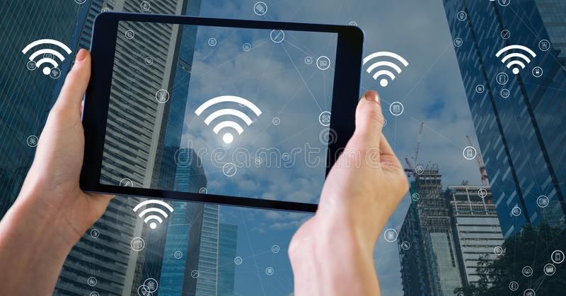 Holding tablet and City with icons of wifi. Digital composite of Holding tablet and City with icons of wifi stock illustration