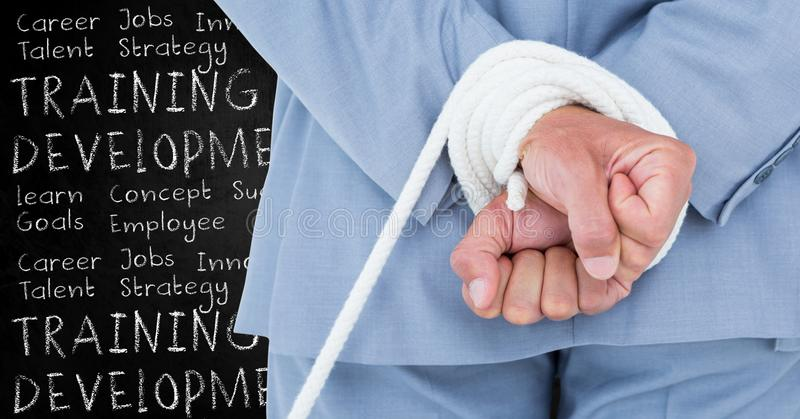 Digital composite image of a businessman with hands tied and training and development concept royalty free stock images