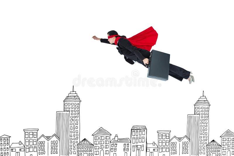 Digital composite image of businesswoman in super hero cape flying over buildings. Digital composite of Digital composite image of businesswoman in super hero stock photography