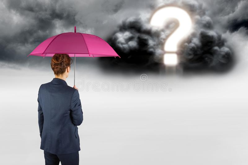 Digital composite image of businesswoman with umbrella looking at question mark in sky royalty free stock photo