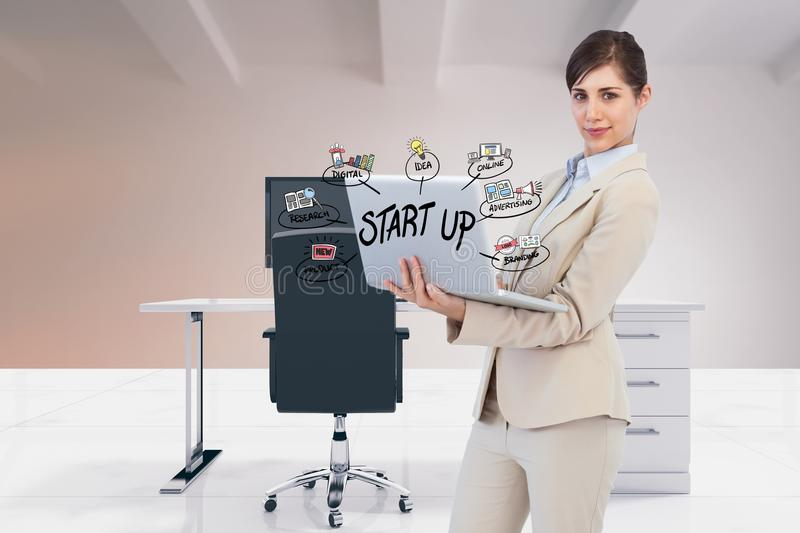 Digital composite image of businesswoman using laptop with start up text and icons in office. Digital composite of Digital composite image of businesswoman using stock image