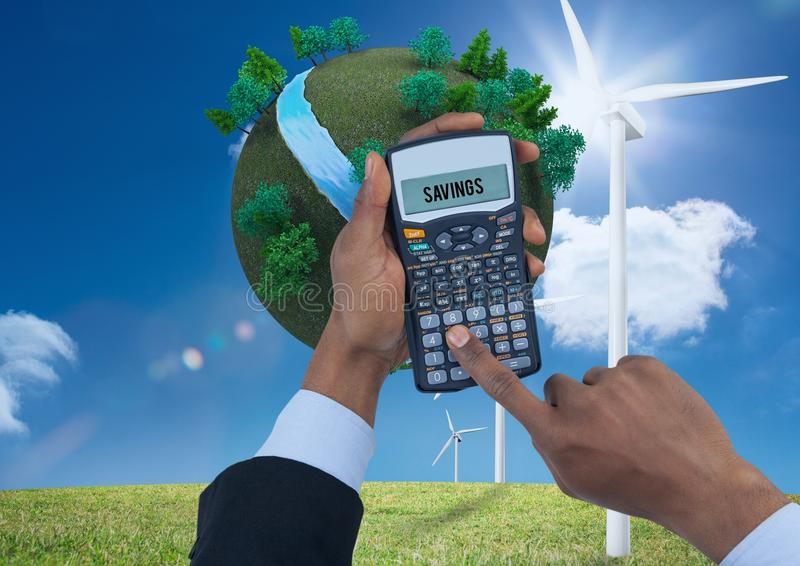 Digital composite image of hands using calculator with planet earth and windmills on grassy field ag stock photography