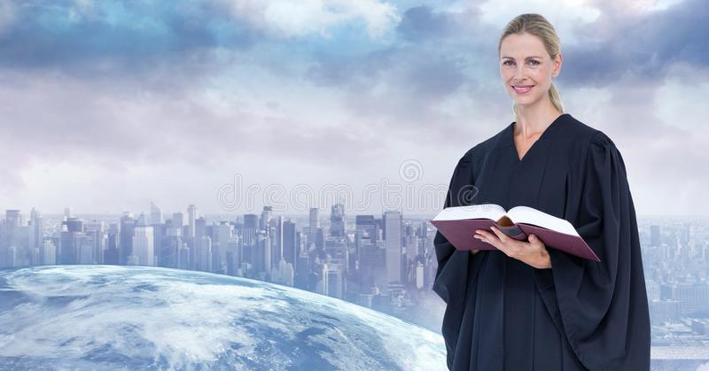 Digital composite image of judge holding book with city in background royalty free stock photo