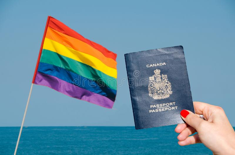 Digital composite of LGBT flag isolated overlooking the ocean with holding Canadian passport on foreground royalty free stock photos