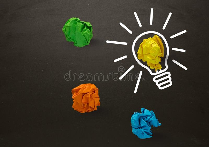 Light bulb with crumpled colorful paper balls and blackboard stock photo