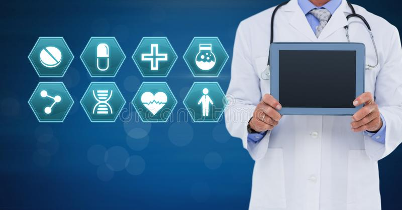 Male doctor holding tablet with medical interface hexagon icons royalty free stock images