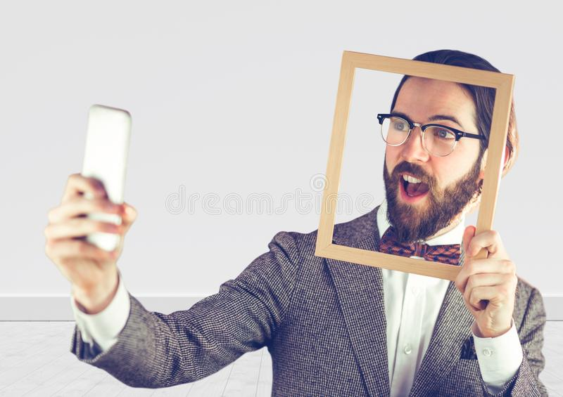 Millennial man holding picture frame and phone stock image