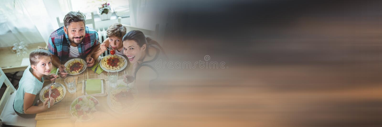 Overhead of family at table with blurry sunset transition. Digital composite of Overhead of family at table with blurry sunset transition stock photo