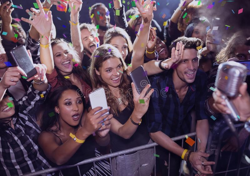 People having fun and making photos at a concert with 3D confetti stock image