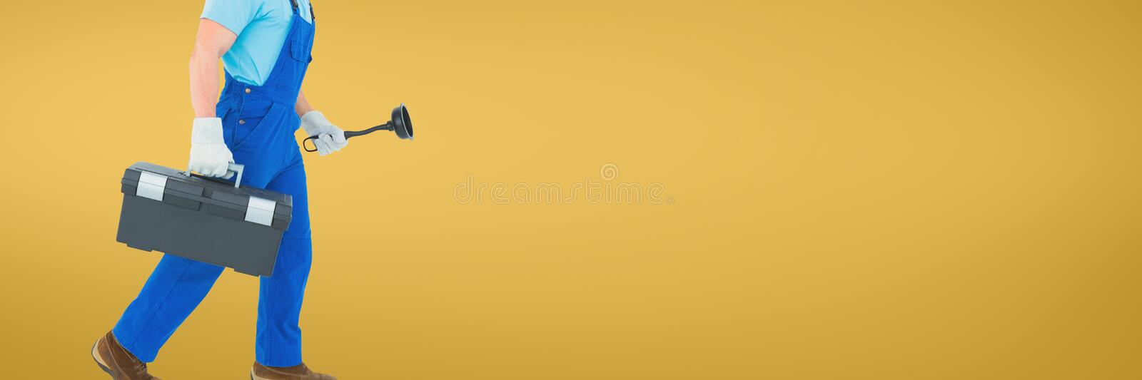 Plumber man holding a plunger and a toolbox against yellow background. Digital composite of Plumber man holding a plunger and a toolbox against yellow background stock photos