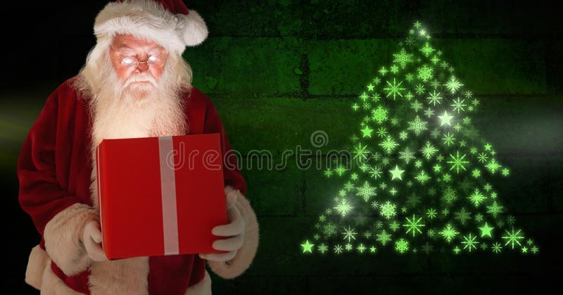Santa holding gift and Snowflake Christmas tree pattern shape glowing green. Digital composite of Santa holding gift and Snowflake Christmas tree pattern shape royalty free stock photography