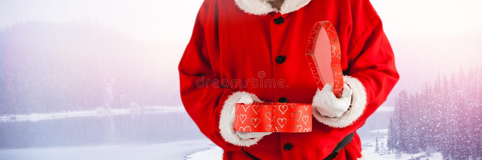 Santa with Winter landscape holding gift. Digital composite of Santa with Winter landscape holding gift stock photography