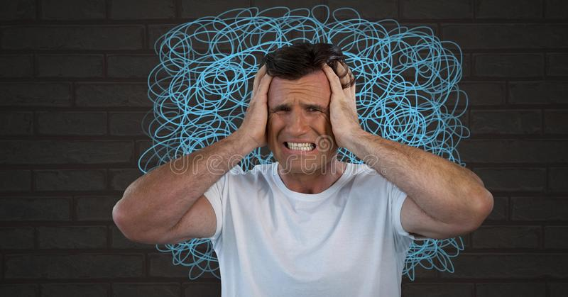 Stressed anxious and frustrated man with intense doodles on wall. Digital composite of Stressed anxious and frustrated man with intense doodles on wall stock images