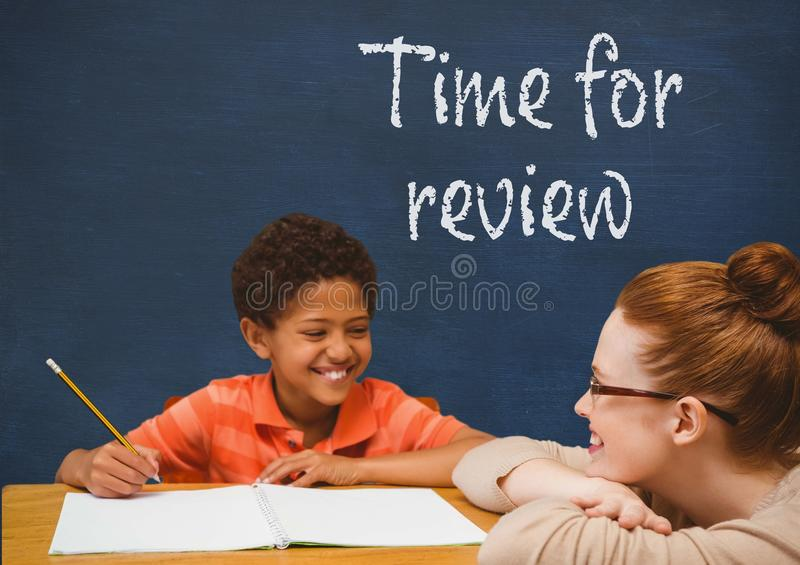 Student boy and teacher at table against blue blackboard with time for review text royalty free stock photos