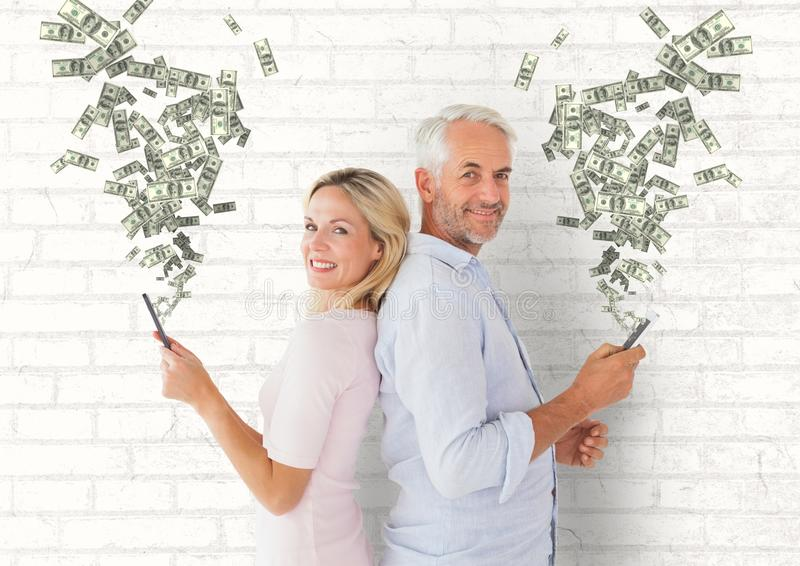 texting money. Senior couple with phones. Money coming up from phones royalty free stock photos
