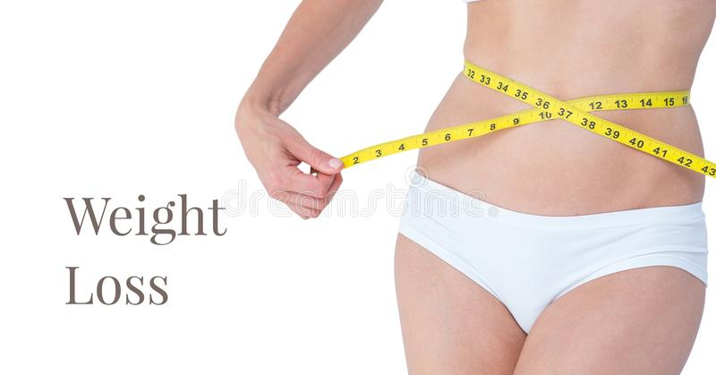 Weight loss text and woman measuring waist. Digital composite of Weight loss text and woman measuring waist stock photo