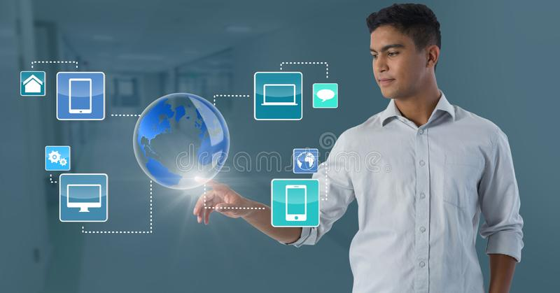 World devices interface and Businessman touching air in front of corridor. Digital composite of World devices interface and Businessman touching air in front of stock images