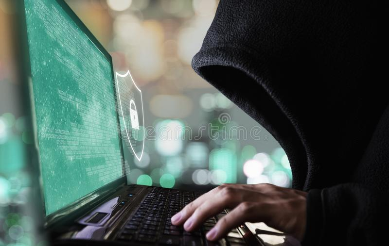 Digital data security system and protection. Anonymous hacker try to hacking on computer laptop royalty free stock photo
