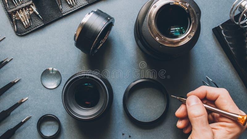 Digital device tech support photo camera lens. Digital device tech support. Top view of man hands repairing photo camera optical dslr lens stock images