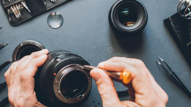 Digital device tech support photo camera lens. Digital device tech support. Top view of man hands repairing photo camera optical dslr lens royalty free stock images