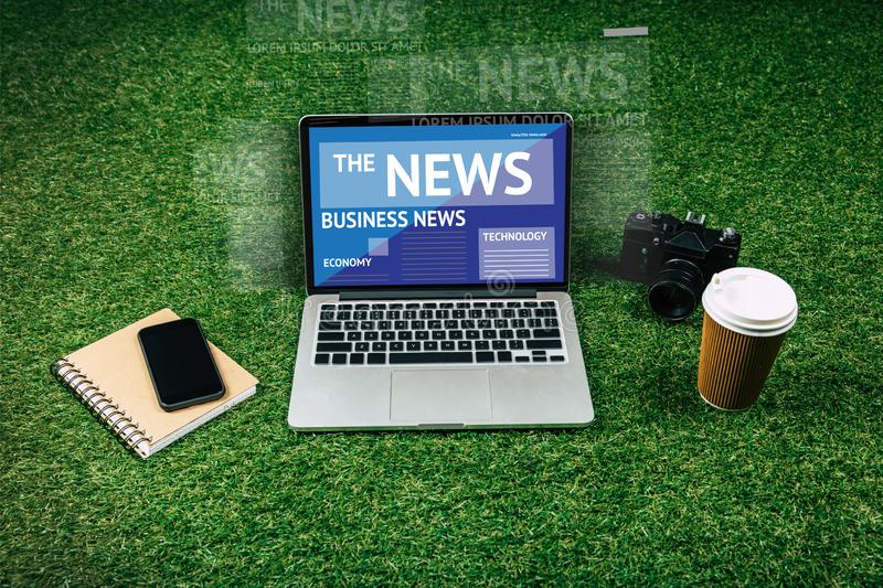 Digital devices and coffee to go. Laptop, smartphone, photo camera and coffee to go in disposable cup on green grass stock photo