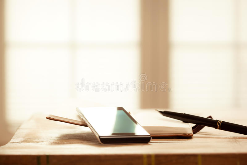Digital Devices on Wooden Table, Blurred windows background, Smartphone with Note Book and Pen stock images