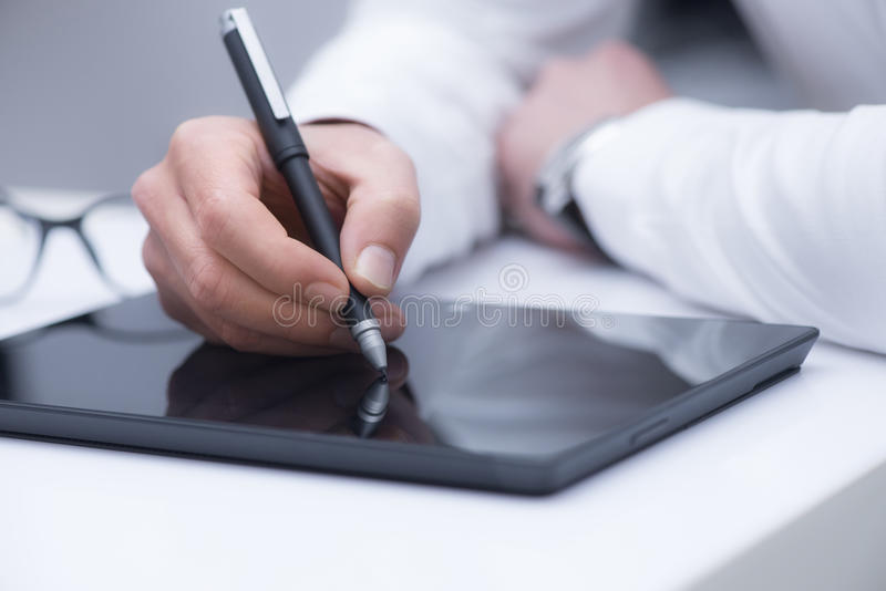 Digital drawing or writing with stylus. One man drawing or writing in a black tablet pc with a black stylus and glasses behind. Cool color scene stock photography