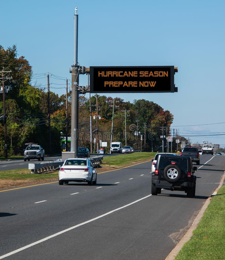 Digital electronic mobile road warning sign that says Hurricane Season prepare now, over a busy highway. Digital electronic mobile road warning sign that says stock image
