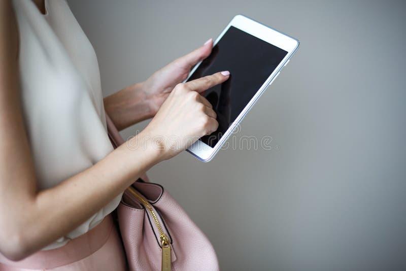 Digital elektronisk minnestavla på händer för kvinna` ett s Läderljus - rosa handväska, elegant stil för sommar royaltyfri foto