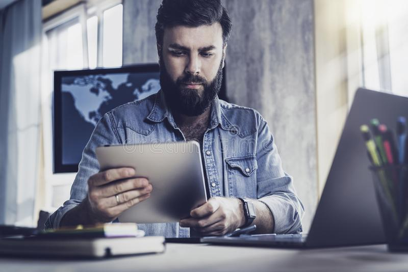 Web developer using wireless connected devices for work. Office manager sitting at desk and working on laptop and tablet stock photography