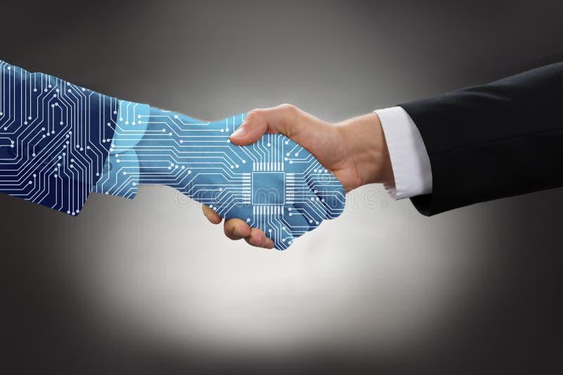 Digital erzeugte menschliche Hand und Geschäftsmann, der Hände rüttelt lizenzfreies stockbild