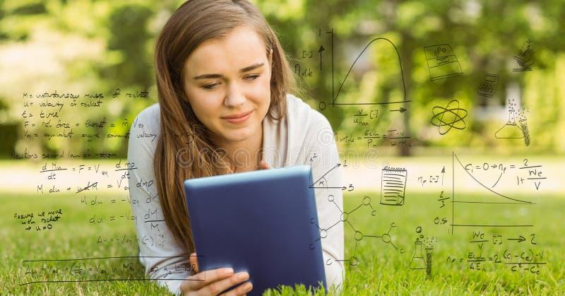 Digital erzeugtes Bild von verschiedenen Gleichungen mit dem lächelnden Studenten, der herein digitale Tablette verwendet stockfoto