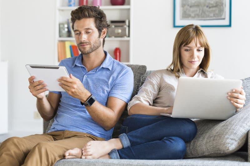 Digital familj på soffan i modern vit lägenhet arkivbild