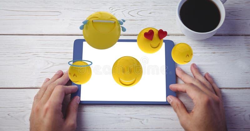 Digital frambragd bild av olika emojis som flyger över handen genom att använda den digitala minnestavlan på trätabellen stock illustrationer