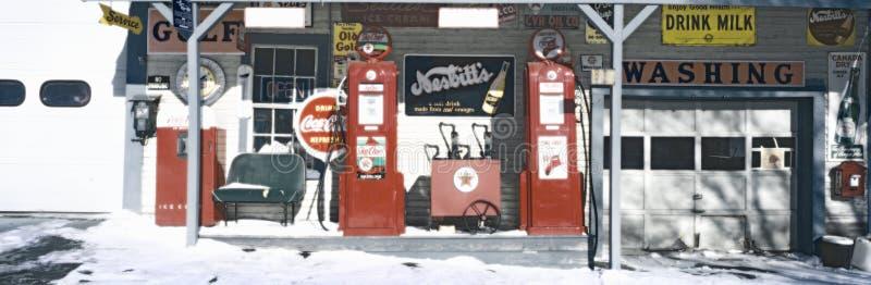 Digital geänderte Ansicht einer WeinleseTankstelle mit im altem Stil Pumpen und vielen altmodischen Zeichen lizenzfreies stockbild